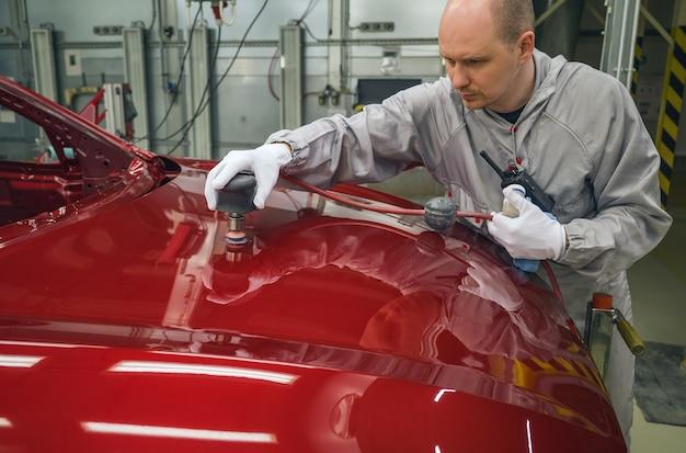 Werknemer van een autofabriek maalt de motorkap van het lichaam