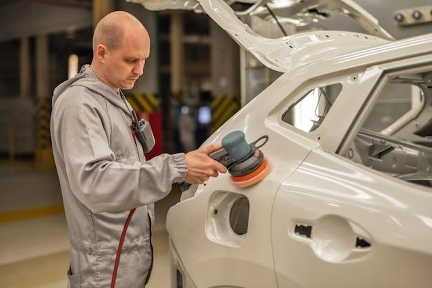 Werknemer van een autofabriek polijst het geverfde oppervlak van de carrosserie