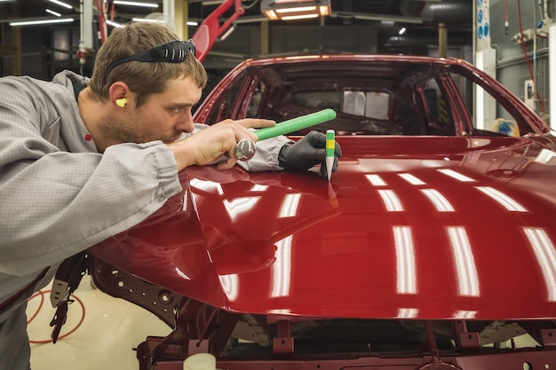 Werknemer van een autofabriek repareert een klein defect met speciaal handgereedschap