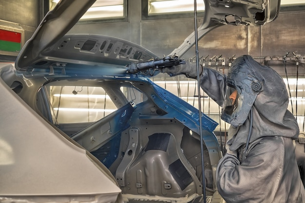 Werknemer van een autofabriek schildert carrosseriedelen