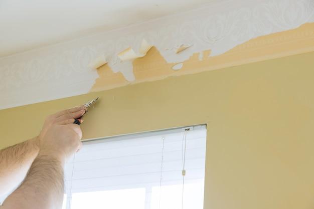 Werknemer van een oud behang van de muur verwijderen