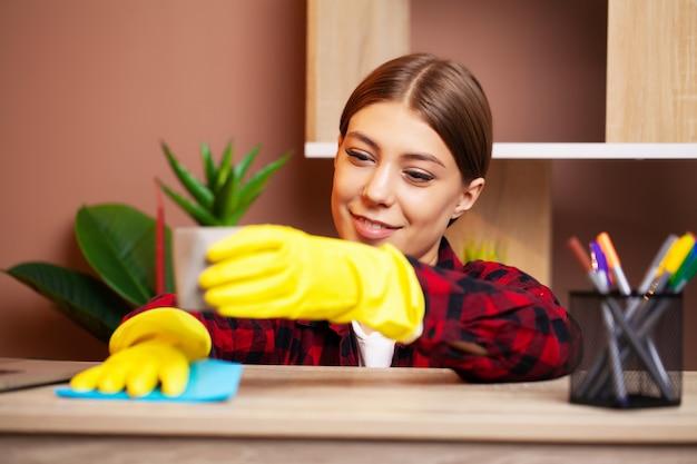 Werknemer van een schoonmaakbedrijf in overall en gele handschoenen maakt het kantoor schoon