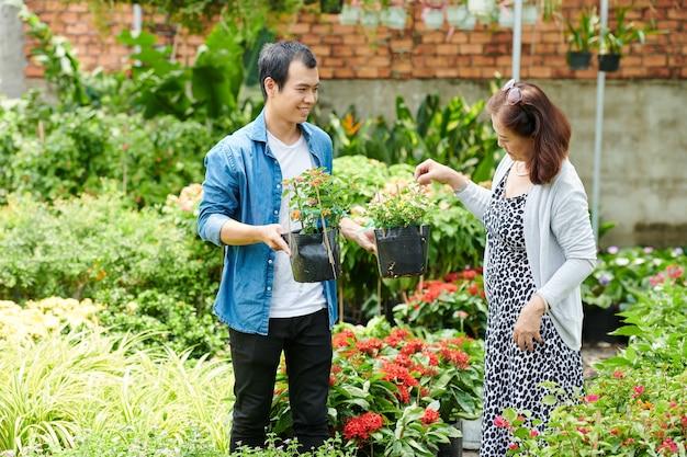Werknemer van het tuincentrum die planten toont