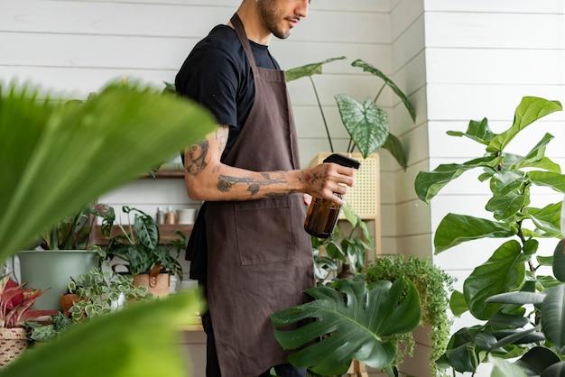 Werknemer van kleine bedrijven vernevelt planten met een waternevel