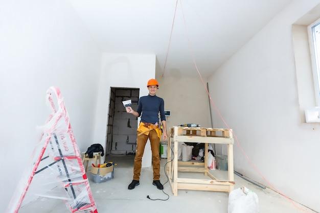 Werknemer veegt de naden buiten het bakstenen huis. de bouwer verwerkt het metselwerk. bouw metselaar werknemer metselaar installeren rode baksteen met troffel plamuurmes buitenshuis.