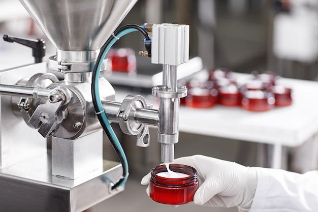 Werknemer vulling container met crème in cosmetische fabriek