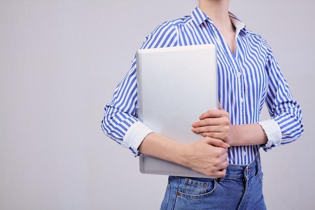 Werknemer, zakelijke dame. een vrouwelijke manager kijkt opzij met een glimlach in een gestreept shirt met zwarte bril en een laptop aan haar rechterhand op een grijze rug.