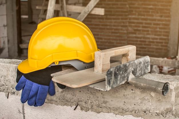 Werknemer zet een helm en gereedschap na het werk.