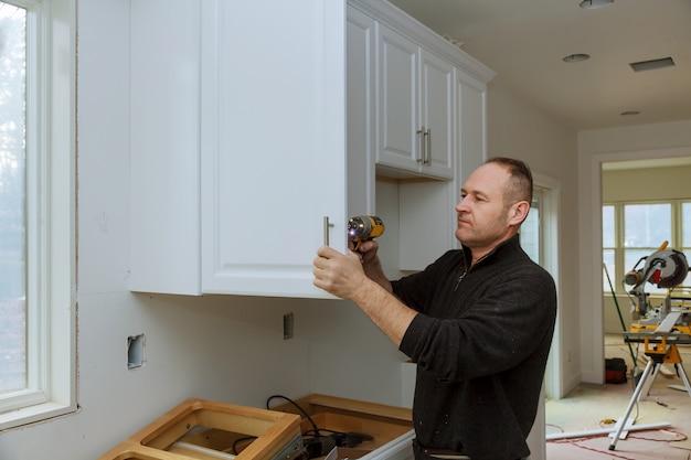 Werknemer zet een nieuwe handgreep op de witte kast met een schroevendraaier die keukenkasten installeert