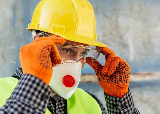 Werknemer zijn beschermende bril aanpassen terwijl het dragen van masker en handschoenen