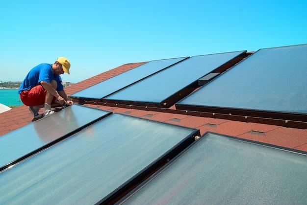 Werknemer zonne-water-verwarmingspanelen op het dak.