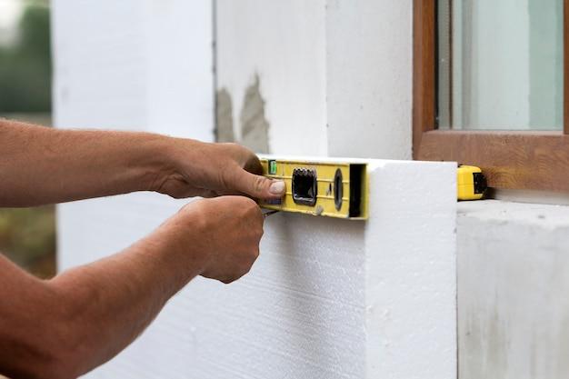 Werknemerhand met niveau en mes meten en snijden van witte harde polyurethaanschuimplaat