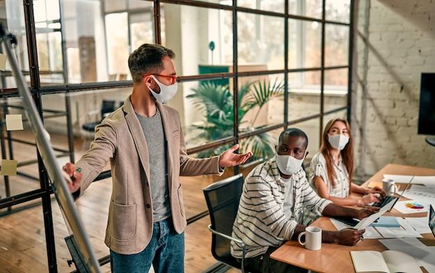 Werknemers bespreken en ontmoeten elkaar terwijl ze een medisch masker dragen ter bescherming tegen het coronavirus. een jonge man schrijft een mindmap op een whiteboard en maakt nieuwe businessplannen tijdens de covid-19-pandemie.
