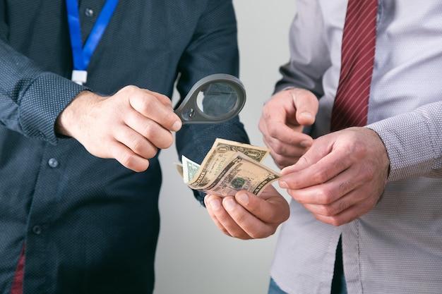Werknemers controleren geld met een vergrootglas.