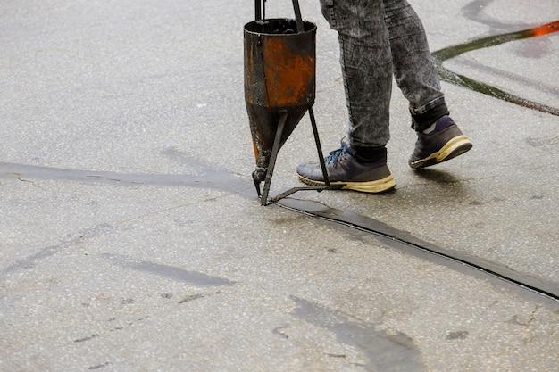 Werknemers die blacktop sealer toepassen op asfalt, een restauratiewerk voor een beschermende laag op de weg