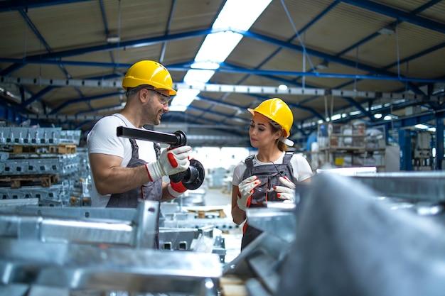 Werknemers die de kwaliteit van metalen onderdelen controleren die in de fabriek zijn vervaardigd