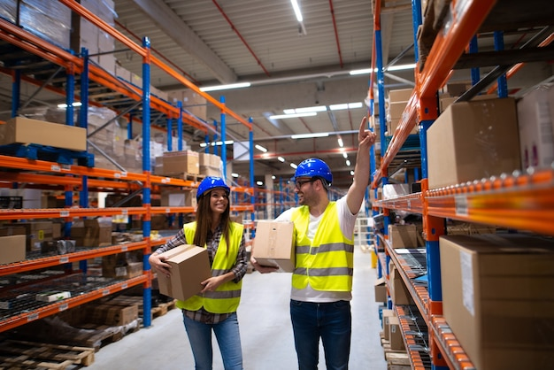 Werknemers die dozen dragen en items verplaatsen in een groot magazijncentrum