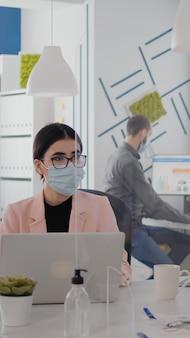 Werknemers die een beschermend gezichtsmasker dragen, praten over het typen van zakelijke projecten op pc op kantoor tijdens de wereldwijde pandemie van het coronavirus