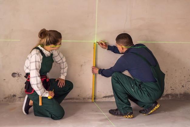 Werknemers die muren meten met laserwaterpas