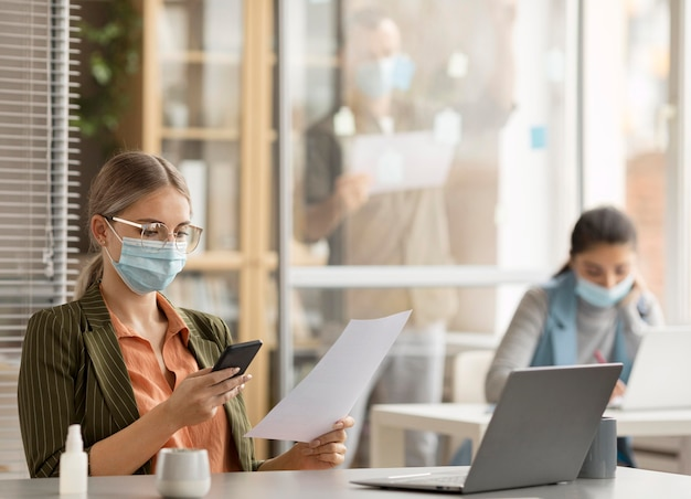 Werknemers die op kantoor gezichtsmaskers dragen