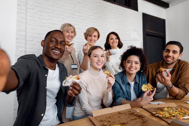 Werknemers die pizza eten op het werk