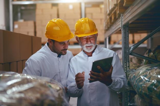 Werknemers die tablet in magazijn.