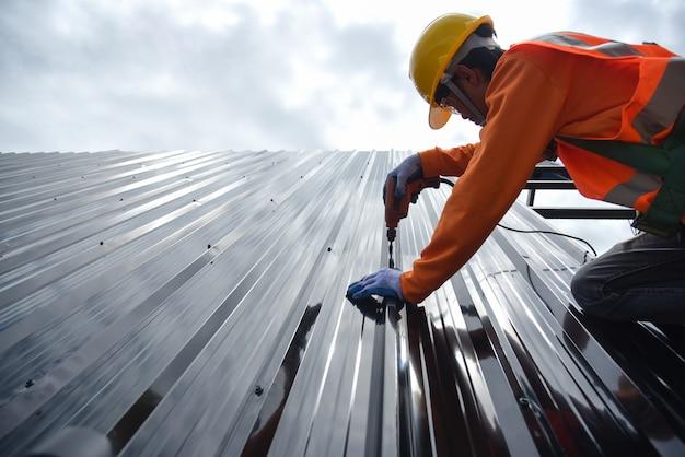 Werknemers dragen beschermende kleding. ano roofer werkt aan de dakconstructie van een gebouw op een bouwplaats. roofer gebruikt een luchtpistool of luchtpistool en installeert een nieuwe metalen plaat op het dak.