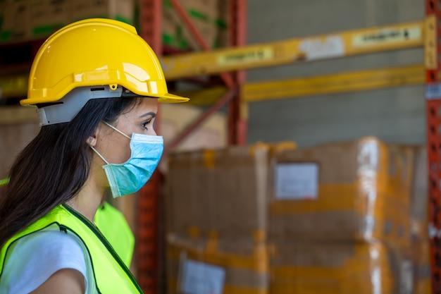 Werknemers dragen een beschermend masker om te beschermen tegen covid-19 in magazijn.