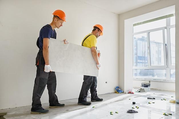 Werknemers dragen een grote keramische tegel voor installatie op de vloer.