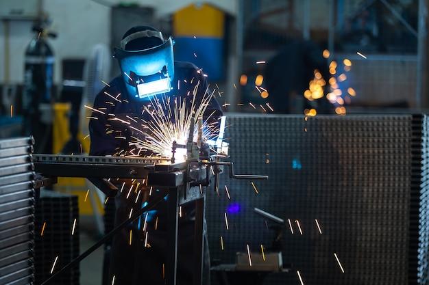 Werknemers dragen industriële uniformen en gelast ijzeren masker bij stalen lasinstallaties.