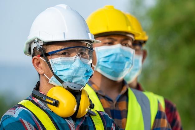 Werknemers dragen voor hun veiligheid beschermende gezichtsmaskers bij het werken op zonne-energiecentrale, coronavirus is een wereldwijde noodsituatie geworden.