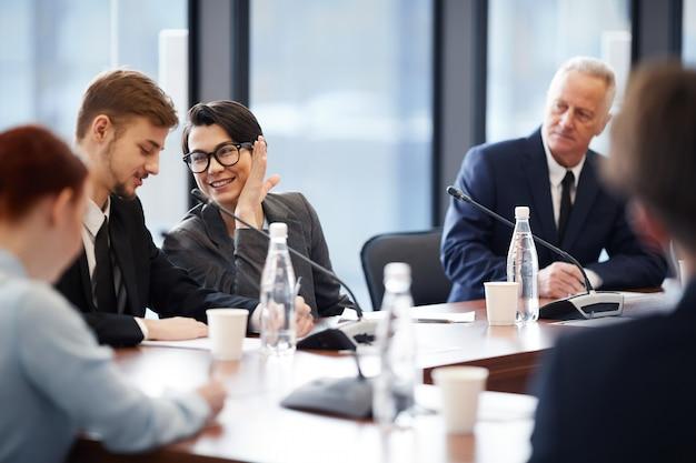 Werknemers fluisteren in zakelijke bijeenkomst