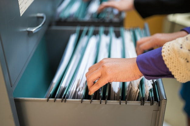 Werknemers gebruiken hun handen om documenten in archiefkasten te zoeken