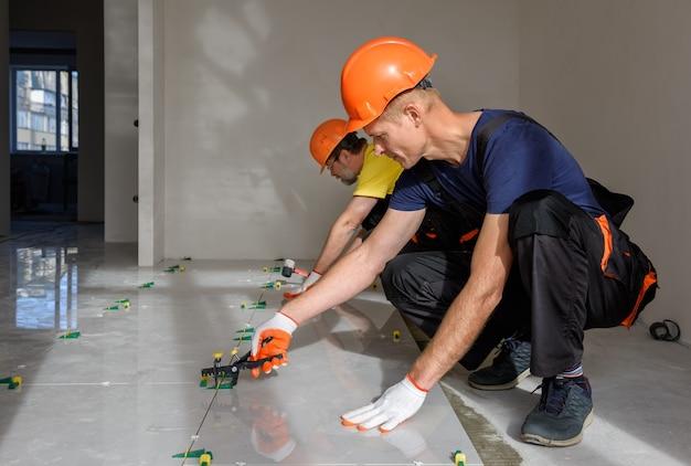 Werknemers gebruiken plastic klemmen en wiggen om de grote keramische tegel te egaliseren