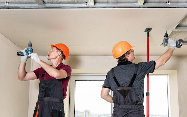 Werknemers gebruiken schroeven en een schroevendraaier om gipsplaat aan het plafond te bevestigen