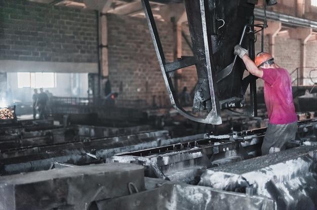 Werknemers gieten nat cement in de vormen. productie van betonplaten