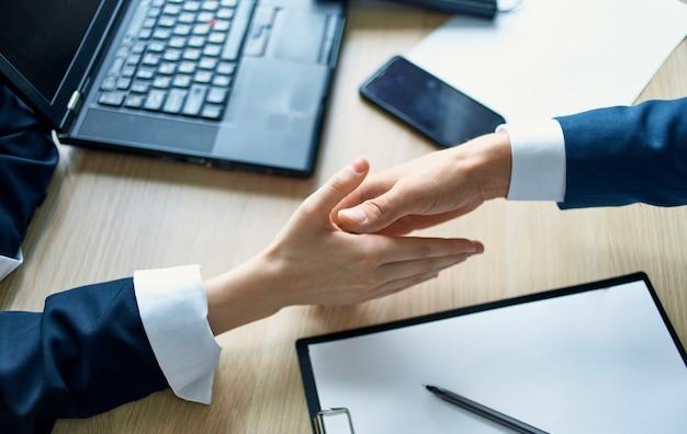 Werknemers handen schudden op het werk in de office-overeenkomst document laptop