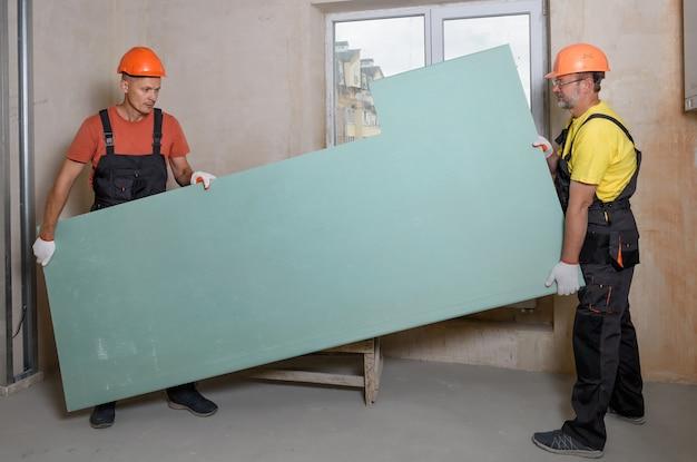 Werknemers houden gipsplaat vast voor verdere bevestiging aan het plafond