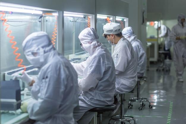 Werknemers in beschermende kleding werken in schone fabrieken