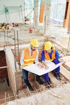Werknemers in de bouw bespreken blauwdruk