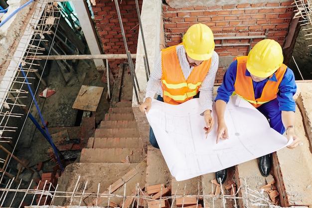 Werknemers in de bouw zitten op de trappen binnenkant van het gebouw en bespreken van de details van de blauwdruk, bekijken van bovenaf