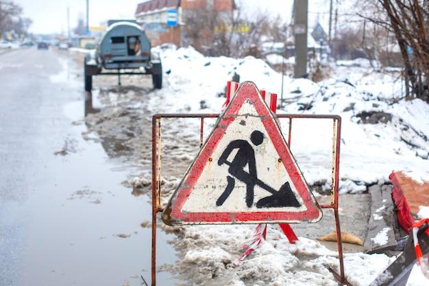 Werknemers in de gemeentelijke nutsbedrijven repareren een gebroken pijp in de winter. uitgegraven put, omheind en met waarschuwingsborden