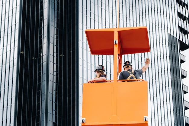 Werknemers in een bouwwieg klimmen op een kraan naar een groot glazen gebouw. de kraan tilt de arbeiders in de autostoel op.