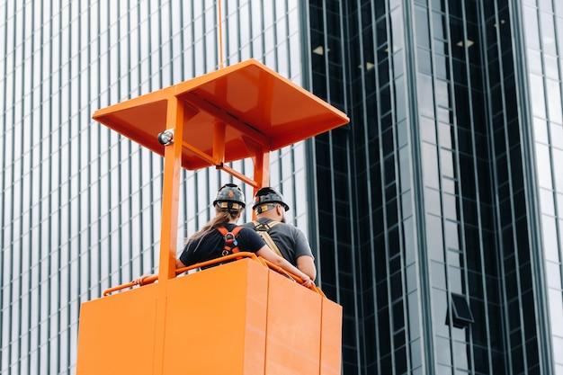 Werknemers in een bouwwieg klimmen op een kraan naar een groot glazen gebouw. de kraan tilt de arbeiders op in de autostoel.