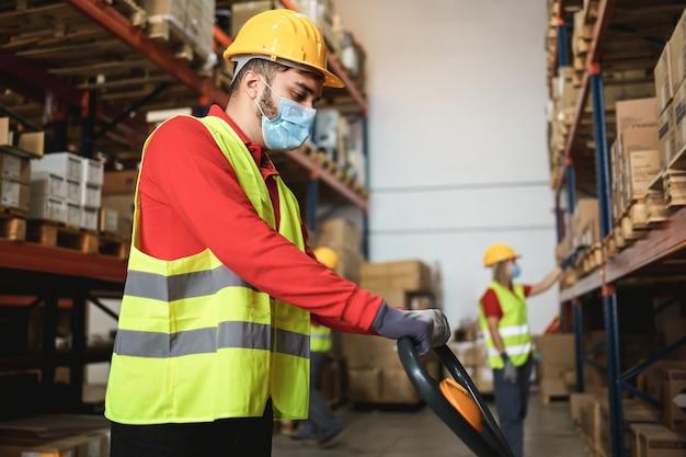 Werknemers in het magazijn die veiligheidsmaskers gebruiken tijdens de uitbraak van het coronavirus