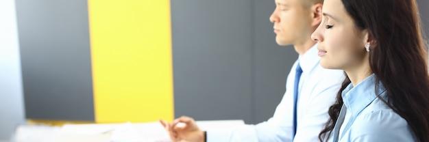 Werknemers in kantoor zitten aan tafel en mediteren close-up