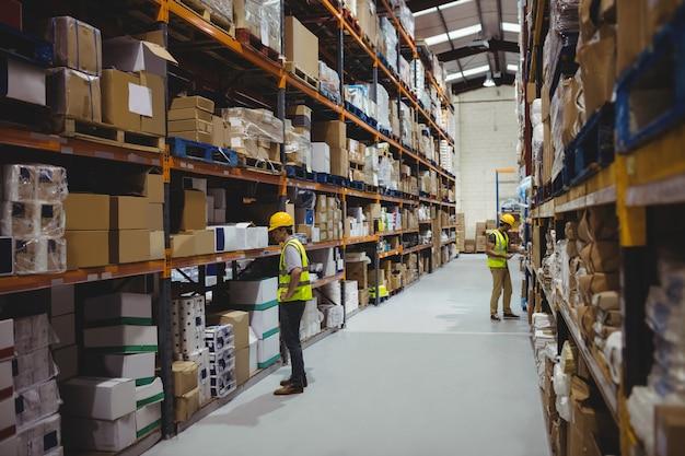 Werknemers in magazijn dragen helmen