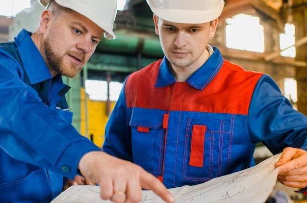 Werknemers in overall en witte beschermende helmen bekijken de tekening