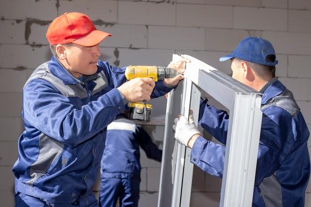 Werknemers installeren beglazing in een huis in aanbouw