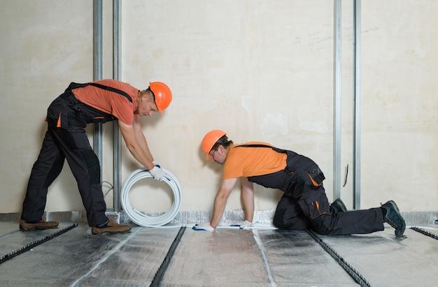 Werknemers installeren een pijp voor de warme vloer in het appartement.